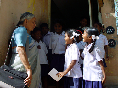 Lakshmi greets some of her eager students. Project funded in part by Asha for Education. Click for a larger version.